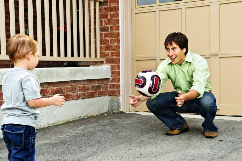 leka fotbollson för fader arkivfoton