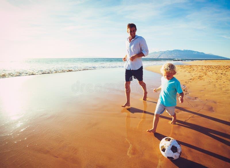 leka fotbollson för fader arkivbilder