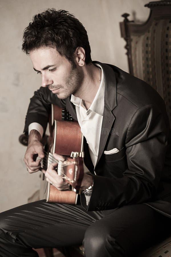 Leka gitarr för ung man royaltyfri foto