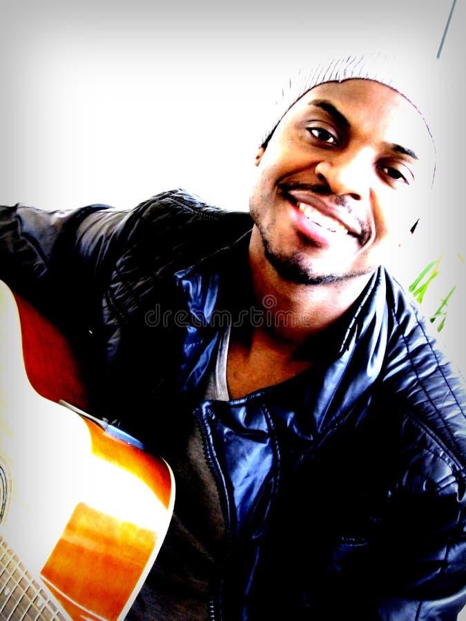 Leka gitarr för ung svart man, inomhus royaltyfria foton