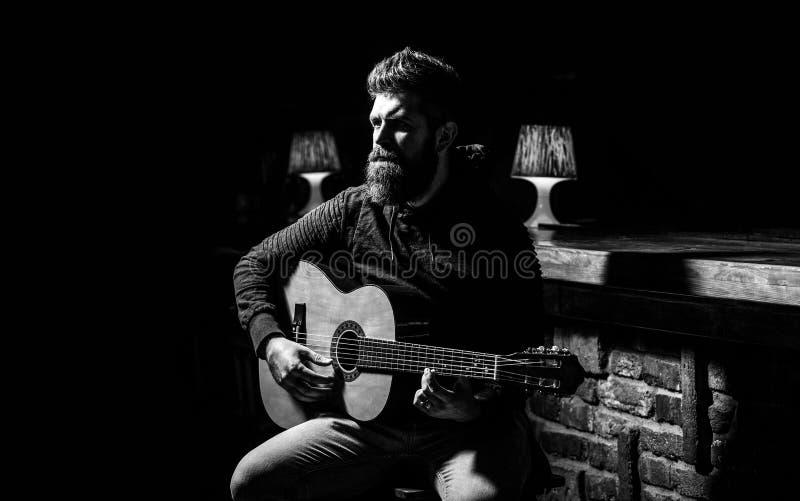 Leka gitarren Skägghipsterman som sitter i en bar Gitarrer och rader Uppsökt man som spelar gitarren som rymmer royaltyfria bilder