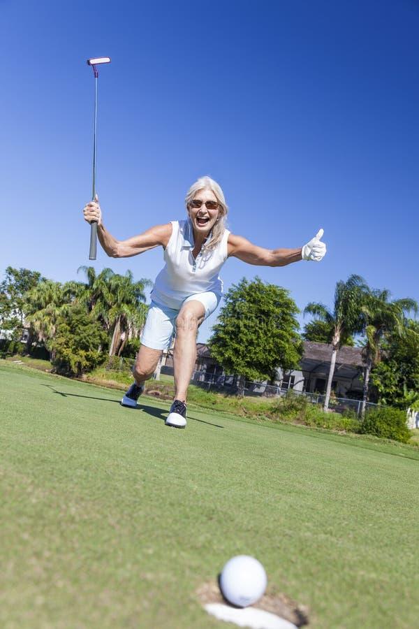 Golf & sätta för lycklig hög kvinna leka royaltyfria bilder