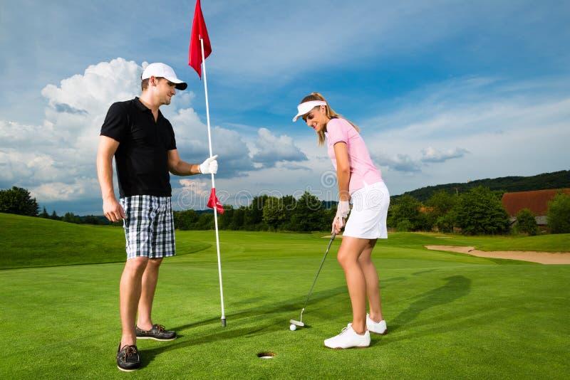 Leka golf för unga sportive par på en kurs arkivbild