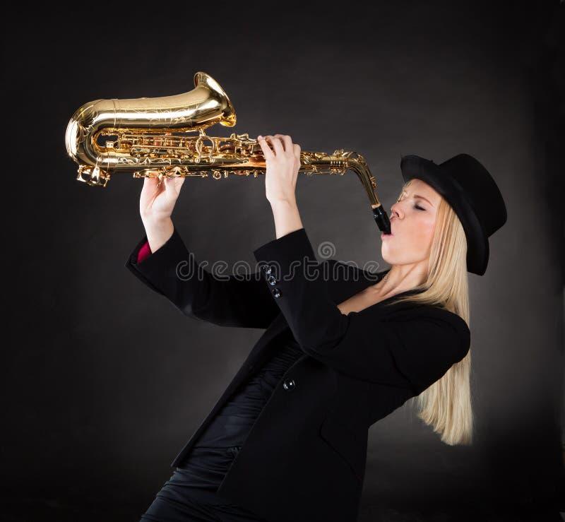Leka saxofon för härlig ung kvinna arkivfoton