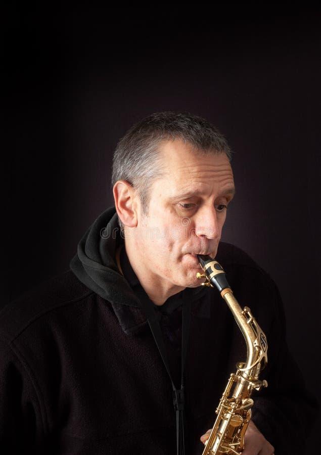leka saxofon för man arkivfoto