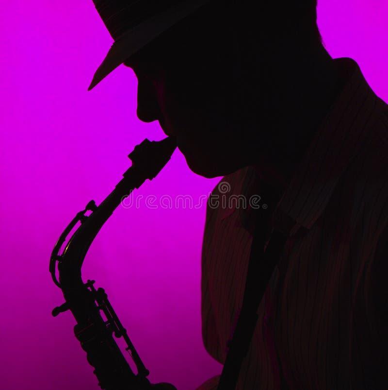leka saxofonsilhouette för man arkivfoton