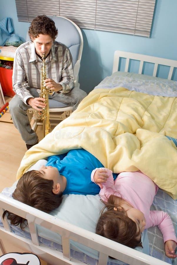 leka saxphone för barndurfader arkivbild