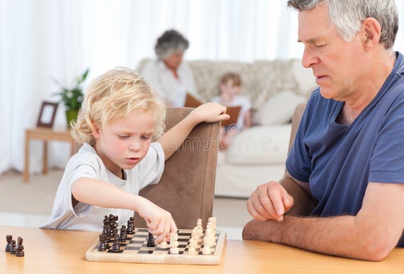 Leka schack för ung pojke med hans farfar royaltyfri foto