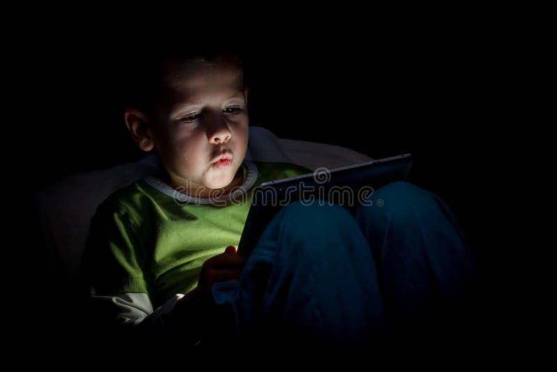 leka tablet för pojkesoffaPC royaltyfri fotografi
