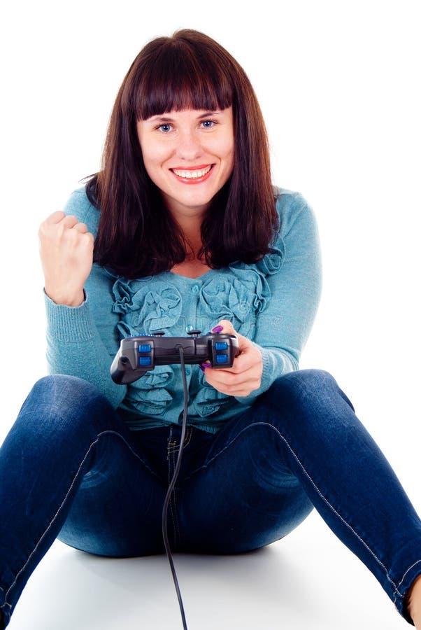 Leka videospel för en flicka som jublar segern fotografering för bildbyråer