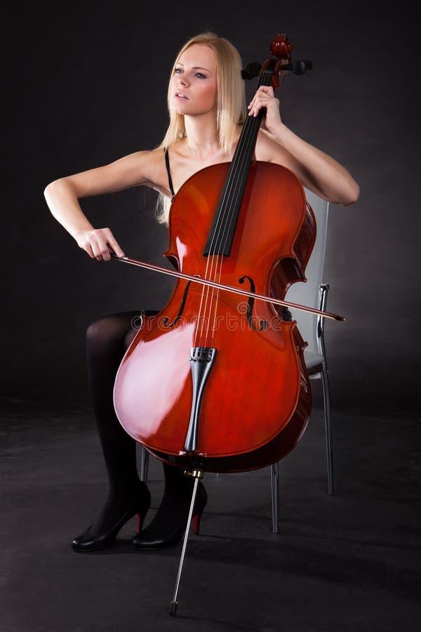 Leka violoncell för härlig ung kvinna royaltyfria foton