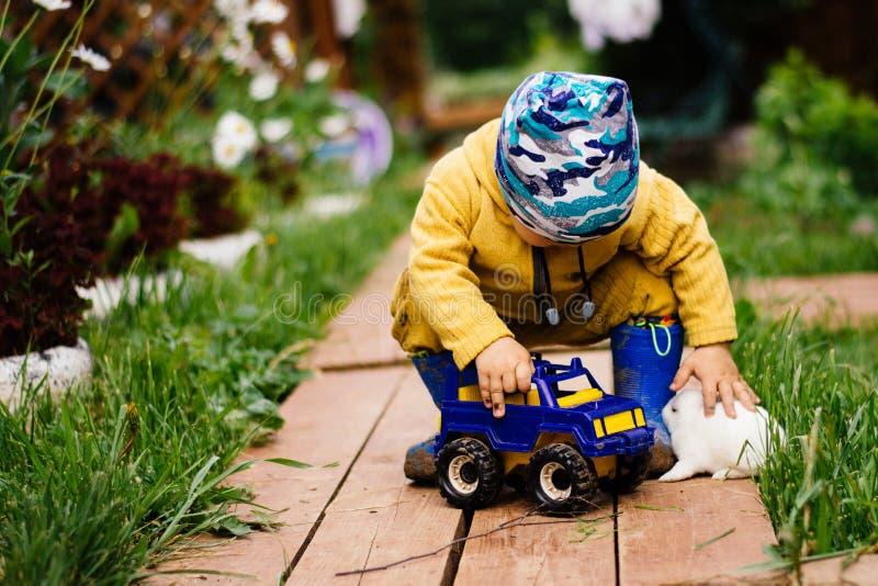Lekar för ett barn med en leksakbil och blickar på den gulliga vita kaninen arkivfoto