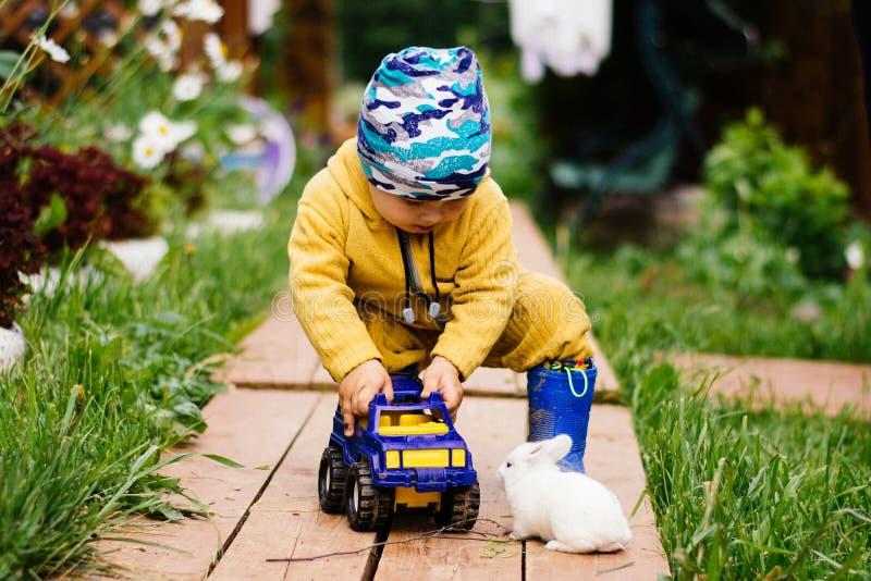 Lekar för ett barn med en leksakbil och blickar på den gulliga vita kaninen royaltyfria foton