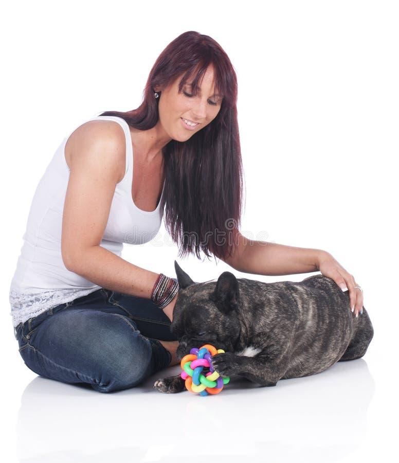 Lekar för ung kvinna med den franska bulldoggen arkivfoton