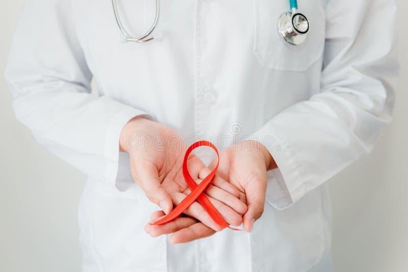 Lekarek ręki Trzymają Czerwonego faborek, pomoce, HIV Międzynarodowy symbol świadomości, opieki zdrowotnej i medycyny pojęcie, Za zdjęcie royalty free