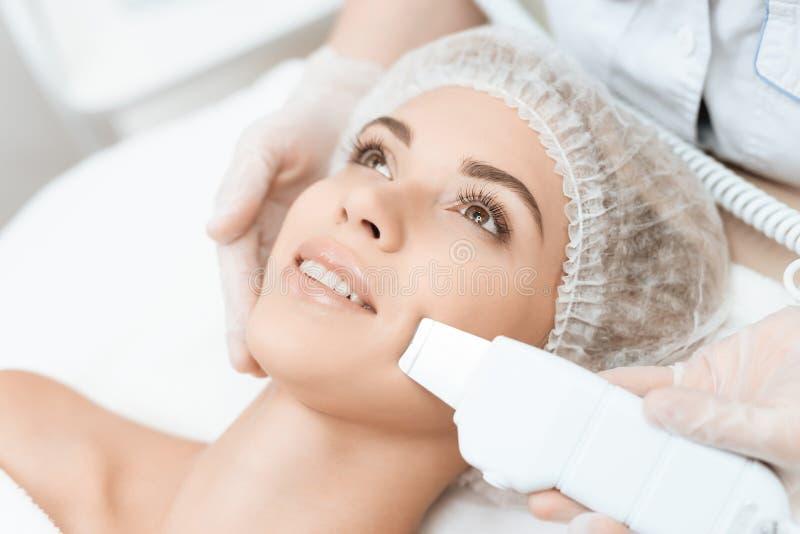 Lekarka czyści kobiety ` s skórę z specjalnym urządzeniem medycznym Kobieta przychodził procedura laserowy włosiany usunięcie zdjęcie royalty free