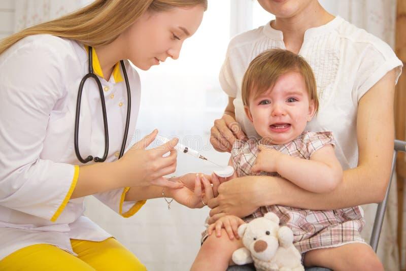 Lekarka daje płaczu dziecku zastrzykowi w domu zdjęcie royalty free