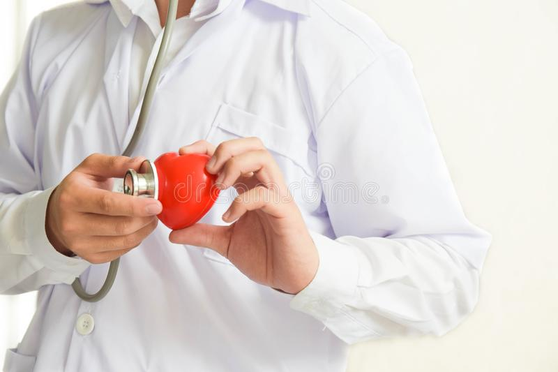 Lekarka egzamininuje czerwoną kierową opiekę zdrowotną i medycznego pojęcie z stetoskopem obrazy stock