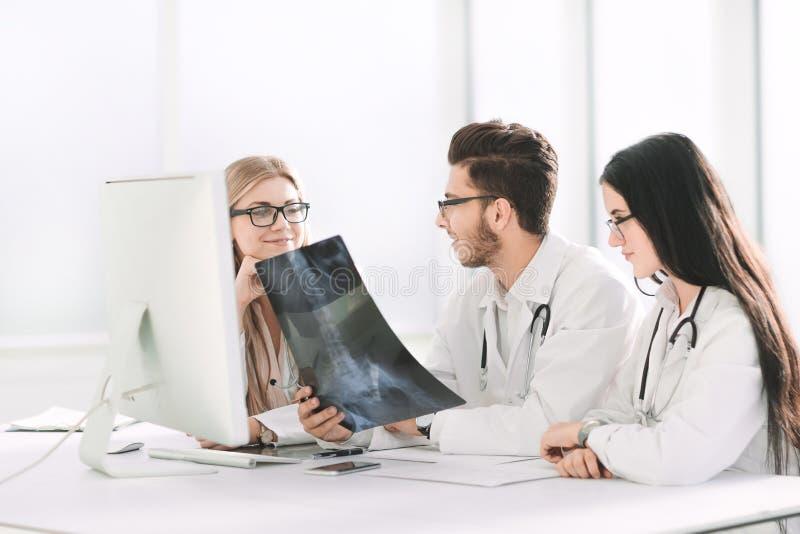 Lekarka eksperci dyskutują promieniowanie rentgenowskie, siedzi przy stołem obrazy stock
