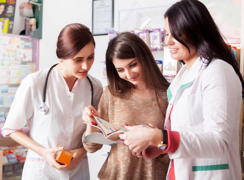 Lekarka i farmaceuta pokazuje katalog klient zdjęcia royalty free
