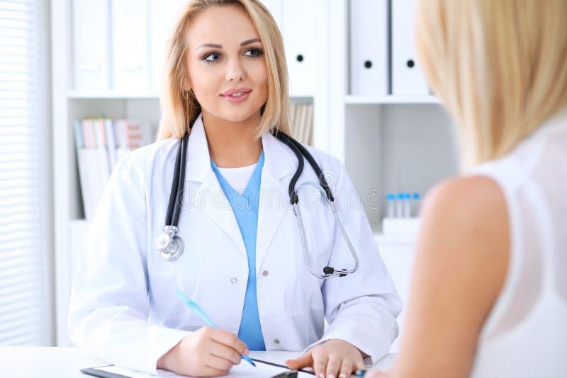 Lekarka i pacjent dyskutuje coś podczas gdy siedzący przy stołem zdjęcia royalty free