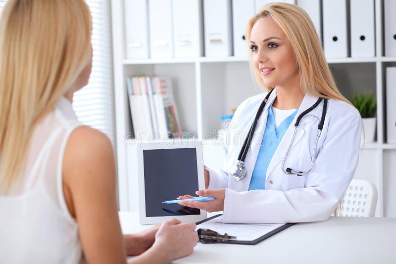 Lekarka i pacjent dyskutuje coś podczas gdy siedzący przy stołem przy szpitalem Lekarz używa pastylka komputer osobistego dla obrazy royalty free