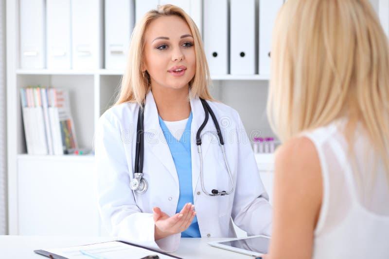 Lekarka i pacjent dyskutuje coś podczas gdy siedzący przy stołem przy szpitalem Medycyny i opieki zdrowotnej pojęcie zdjęcia royalty free