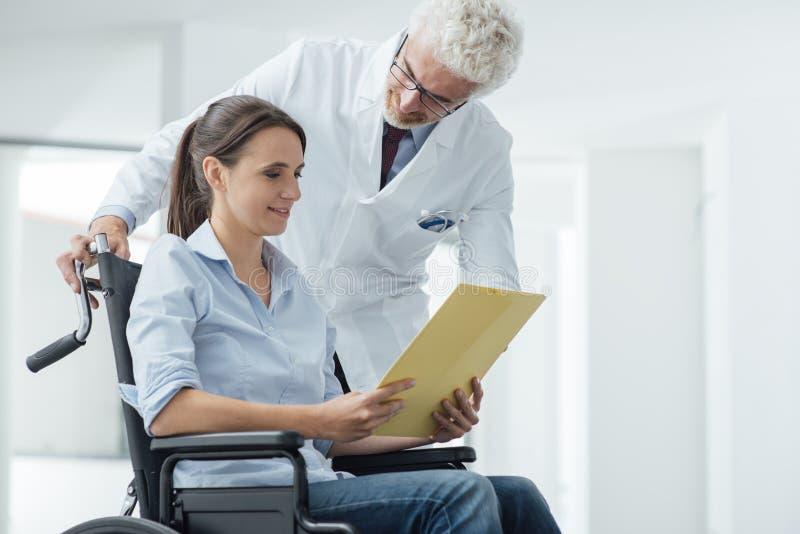 Lekarka i pacjent egzamininuje książeczki zdrowia zdjęcie stock
