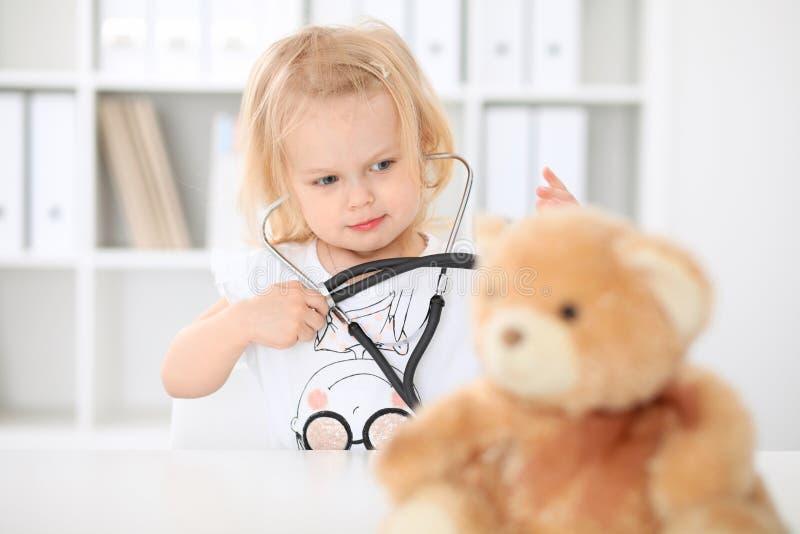 Lekarka i pacjent w szpitalu Mała dziewczynka egzamininuje misia z stetoskopem Opieka zdrowotna, ubezpieczenie i pomoc, fotografia stock