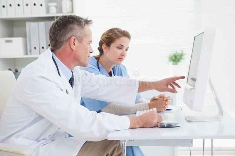 Lekarka i pielęgniarka patrzeje komputer zdjęcie royalty free