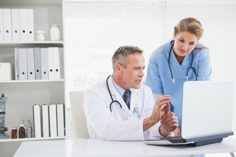 Lekarka i pielęgniarka patrzeje laptop obraz stock
