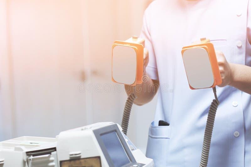 Lekarka jest dawać patient& x27 defibrillators oprócz; s życie w szpitalu zdjęcia stock