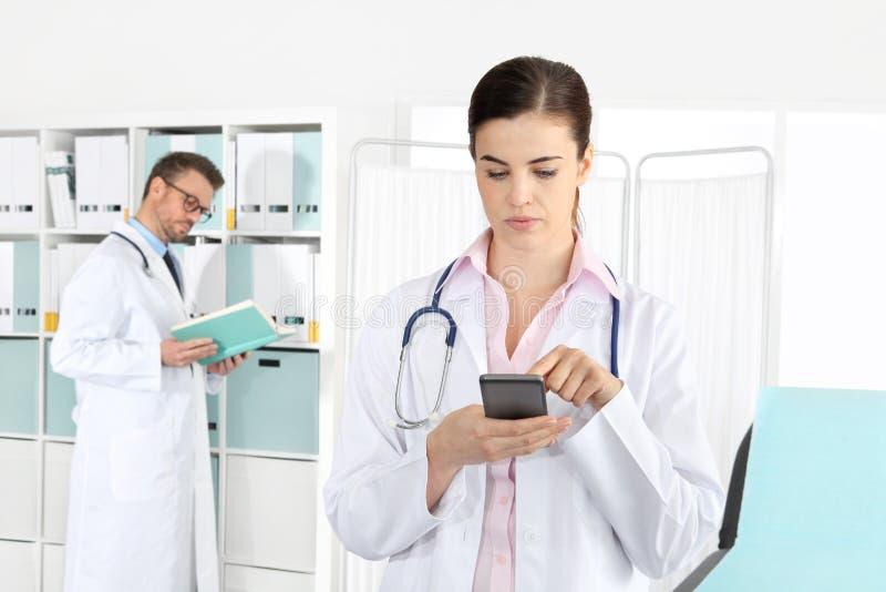 Lekarka na telefonie, z kolegą w medycznym biurze fotografia stock