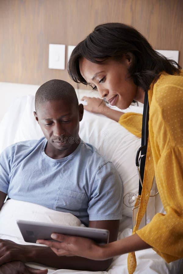 Lekarka Odwiedza I Opowiada Z Męskim pacjentem W łóżku szpitalnym Z Cyfrowej pastylką zdjęcia stock