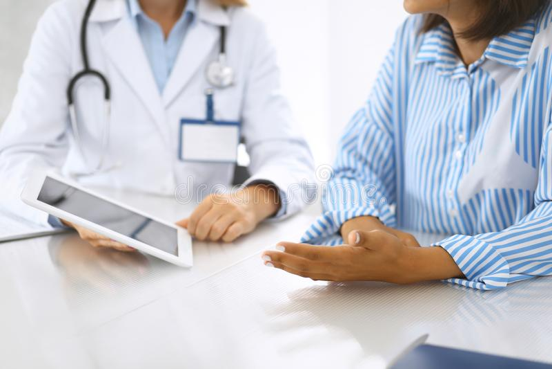 Lekarka, pacjent i podczas gdy siedzący przy biurkiem Lekarz wskazuje w pastylkę p obrazy royalty free