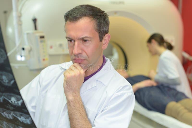 Lekarka patrzeje xrays mri cierpliwego wchodzić do przeszukiwacz w tle obraz stock