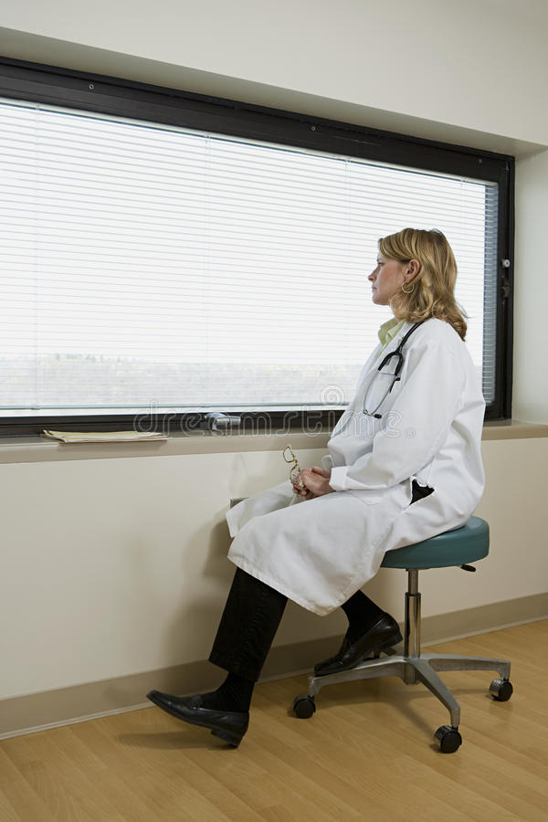 Lekarka patrzeje z okno fotografia stock