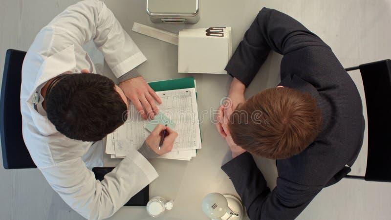 Lekarka pisze wartości pacjent z dużą ceną Odgórny widok zdjęcie stock