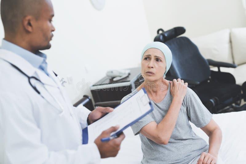 Lekarka przesłuchuje kobiety Kobieta przechodzi rehabilitację po leczenia raka fotografia stock