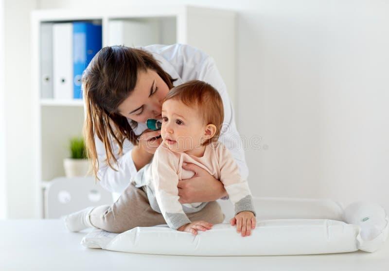 Lekarka sprawdza dziecko ucho przy kliniką z otoskopem zdjęcia stock