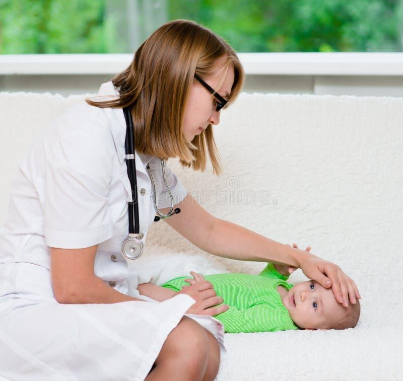 Lekarka sprawdza temperaturę dotyka jego czoło dziecko obrazy stock