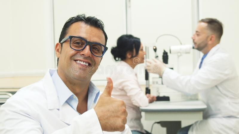 Lekarka stawia dalej szkła i pokazuje aprobaty podczas gdy na tle egzamininuje pacjenta inna lekarka obraz royalty free