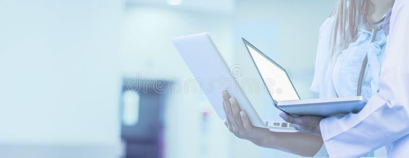 Lekarka trzyma laptop w ręce, tło jest szpitalna, dla sieć sztandaru horyzontalnego panoramicznego stylu, pojęcie sieci medyczna  zdjęcie royalty free