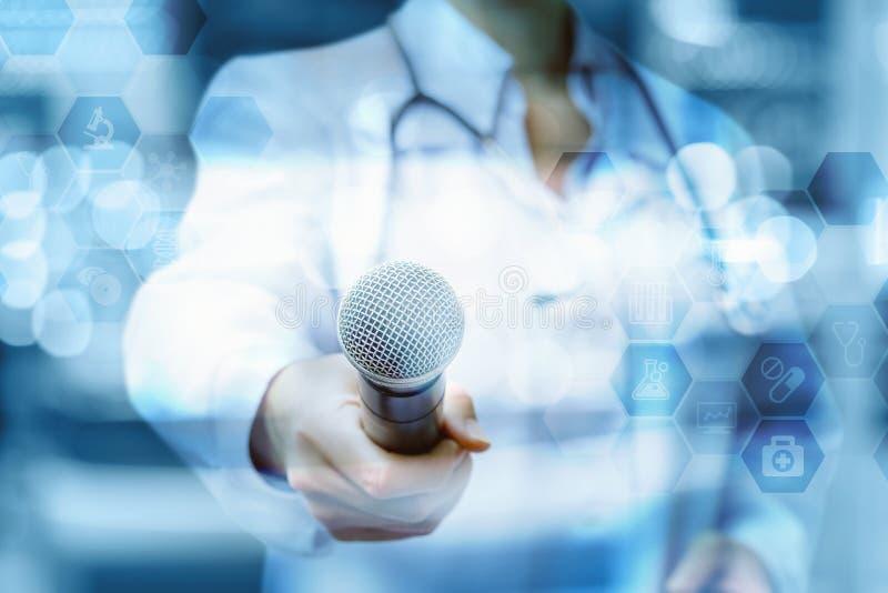 Lekarka trzyma out mikrofon obrazy stock