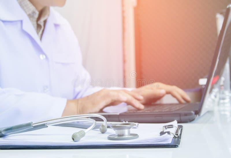 Lekarka używa cyfrowego labtop komputerową medyczną pracującą informację z stetoskopem na biurku fotografia royalty free