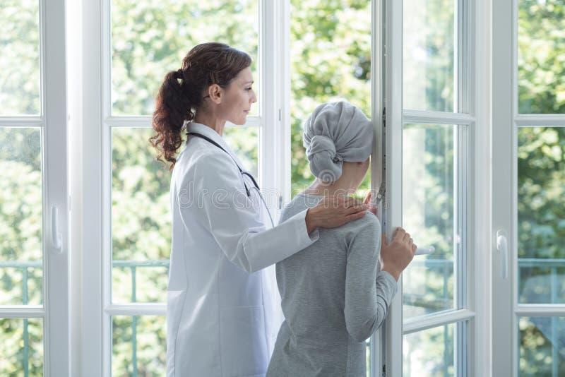 Lekarka w bielu jednolitym pomaga dzieciaku z nowotworem podczas traktowania obrazy stock