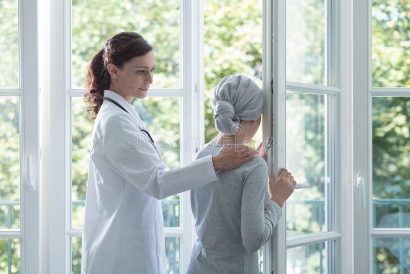 Lekarka w bielu munduru podporowej chorej dziewczynie z chustką na głowę zdjęcia royalty free
