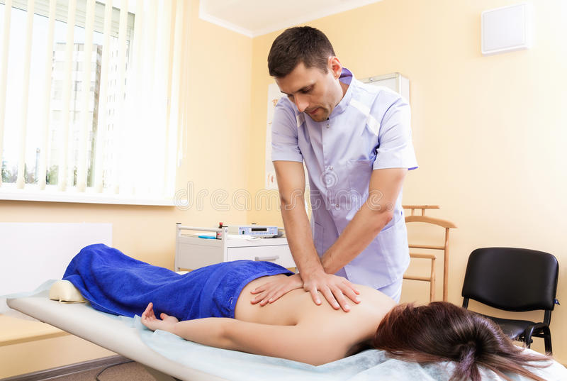 Lekarka w biurowej robi masaż młodej kobiecie mistrzowski masaż masuje jego plecy klient obrazy stock