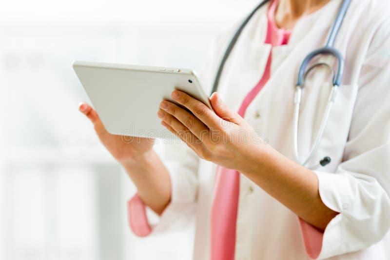 Lekarka w szpitalnym biurze używać pastylka komputer osobistego zdjęcie stock