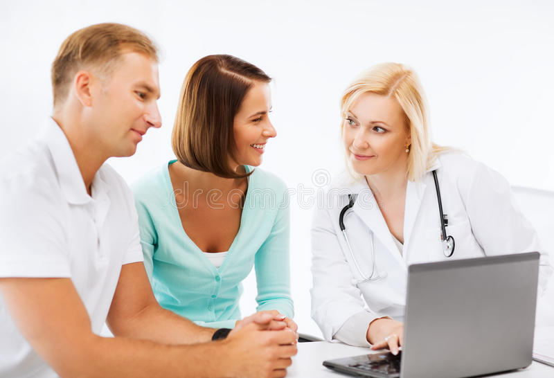 Lekarka z pacjentami patrzeje laptop zdjęcia royalty free